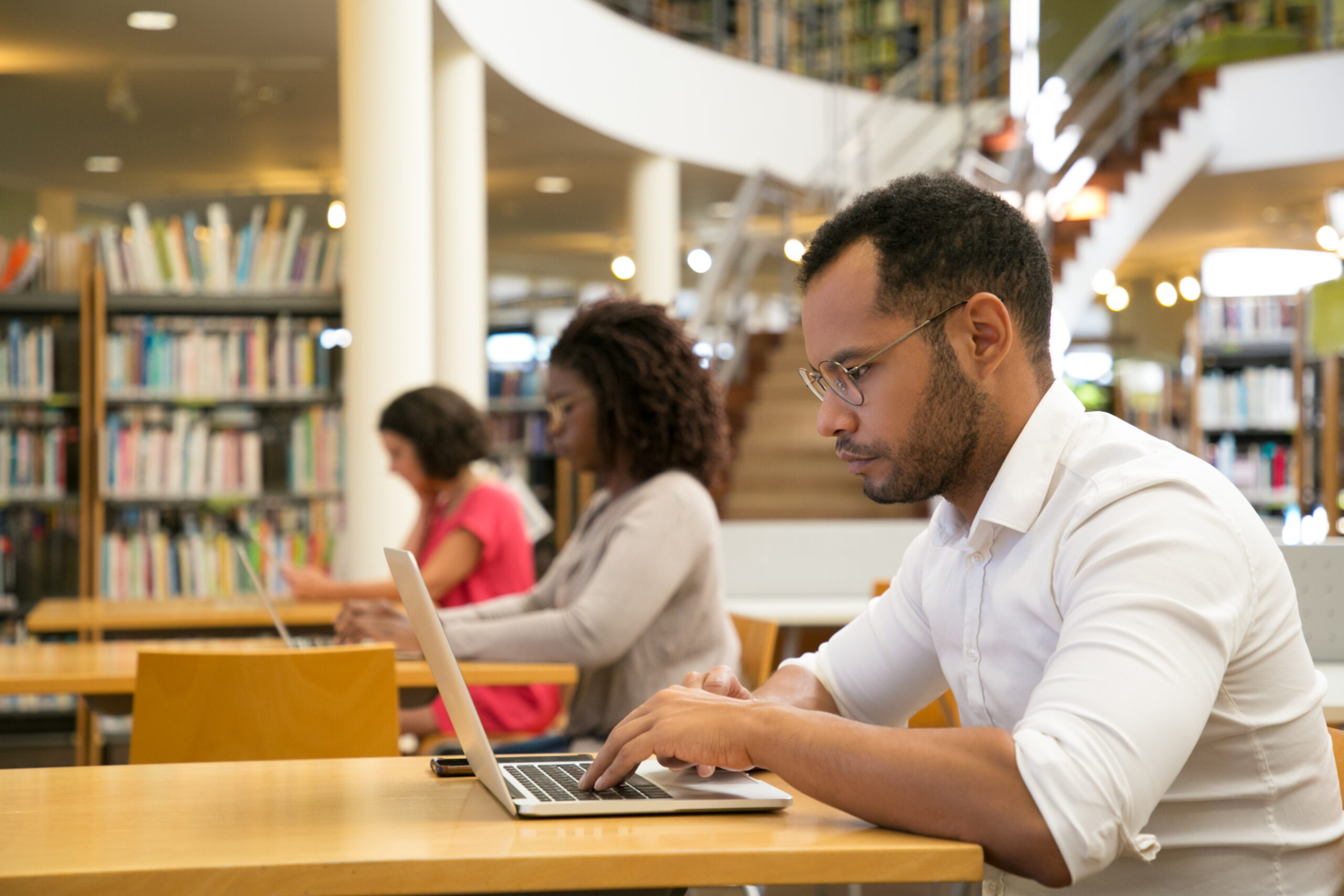 Mix raced trainees working on computer in public library. Serious people sitting at desks and using laptops. Knowledge concept